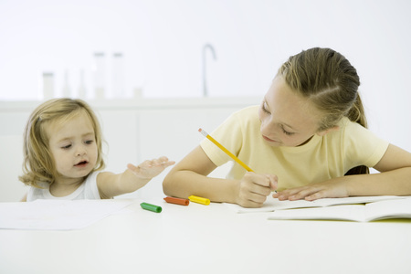 distractions: Girl doing homework, younger sister reaching for markers LANG_EVOIMAGES