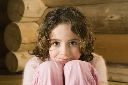Girl sitting with head resting on knees, smiling at camera LANG_EVOIMAGES