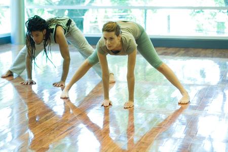 oneself: Two young adults doing prasarita padottanasana pose in yoga class