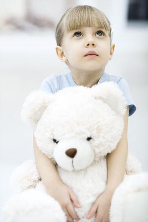 Little girl holding teddy bear, looking up