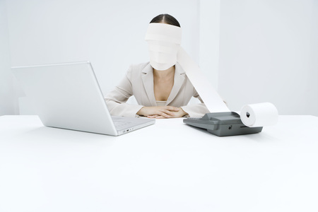 Woman sitting at desk with adding machine and laptop, printout tape wrapped around head