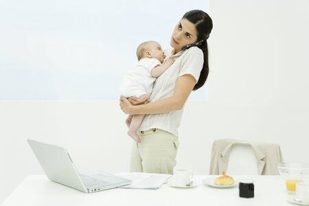 Professional woman standing at breakfast table, holding baby, using cell phone