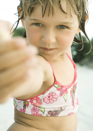 Girl on beach, pointing at camera, close-up