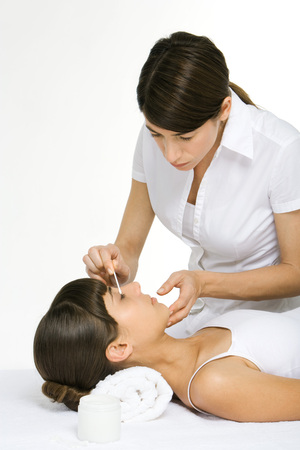 Beautician rubbing cotton swab over womans eyelid