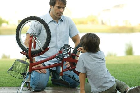 water quality: Father and son fixing bike together