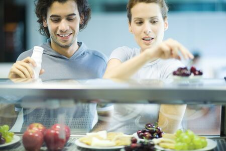 Young adults in exercise clothing, choosing snack in health club cafeteria LANG_EVOIMAGES