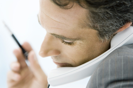 Man holding phone between chin and shoulder, side view, close-up LANG_EVOIMAGES