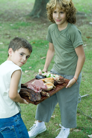 Two boys carrying tray of grilled and raw meats