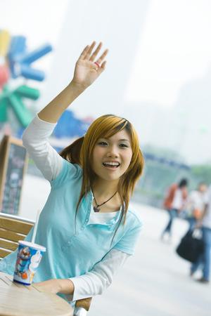 Teenage girl sitting outdoors, waving