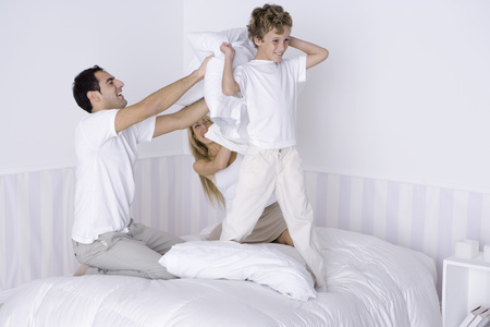 Family having pillow fight on bed
