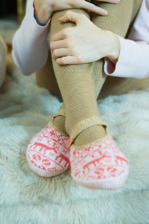Teenage girl hugging knees, wearing tights and slippers, cropped view of legs LANG_EVOIMAGES