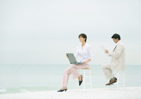 Two business people sitting on stools on beach, one using laptop, the other reading newspaper LANG_EVOIMAGES