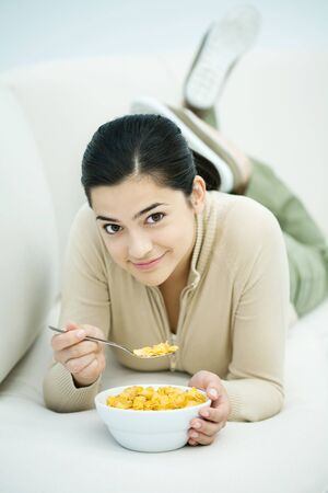 Young woman lying on stomach, eating bowl of cereal LANG_EVOIMAGES