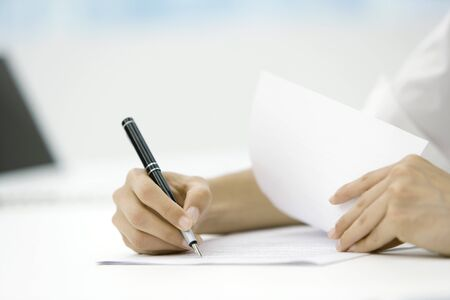 turning the page: Person signing document with pen, cropped view of hands