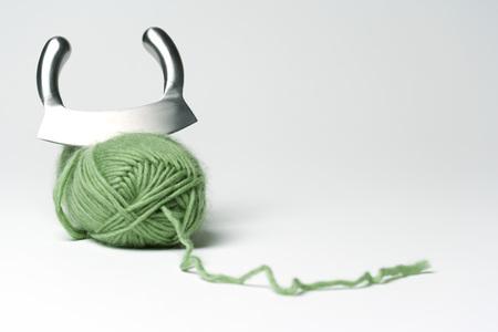 Mincing knife cutting into skein of green yarn