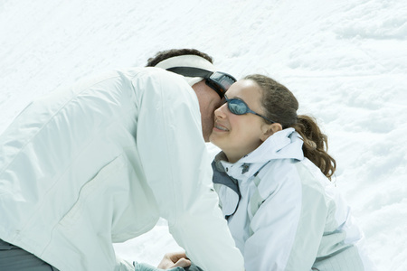 Young friends in snow, male whispering in females ear, female smiling