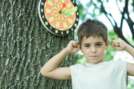 Boy standing next dart board, raising fists