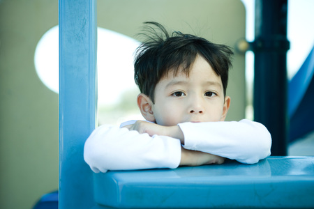 Boy on playground equipment, looking at camera