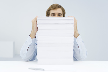 blanks: Man peering over tall stack of paper LANG_EVOIMAGES