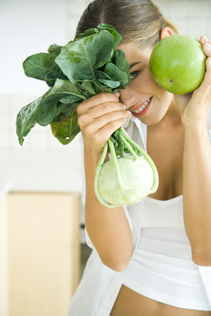Woman holding up and hiding behind fresh kohlrabi and apple, smiling at camera