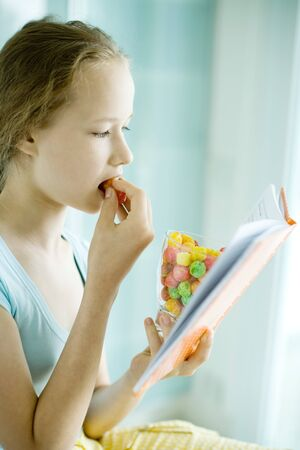 Girl reading and eating dry cereal