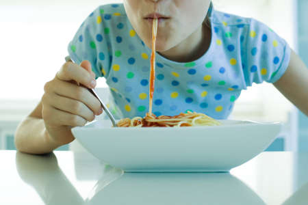 sucks: Girl eating spaghetti with tomato sauce, cropped view LANG_EVOIMAGES