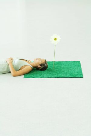 pasto sintetico: Woman lying with head on square of artificial turf LANG_EVOIMAGES