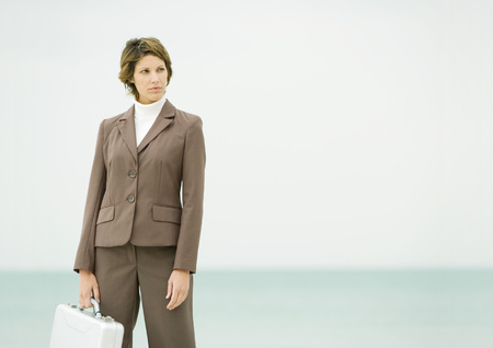 Businesswoman standing on beach LANG_EVOIMAGES