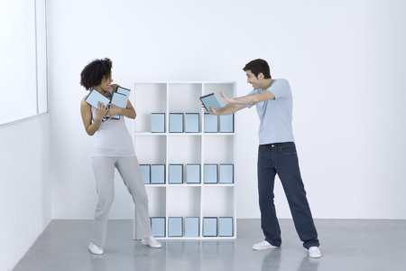 Man and woman joking, fighting over DVDs on shelf