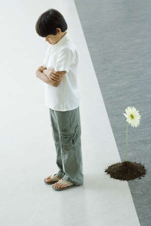 Boy standing with back turned to flower