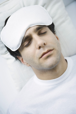 Man reclining with ice pack on his forehead, eyes closed