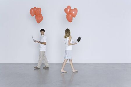 Man and woman walking past each other, both carrying laptop computers and heart balloons LANG_EVOIMAGES