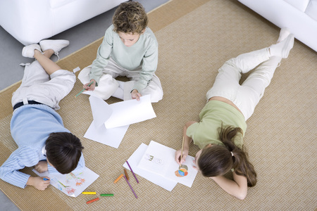 Three children coloring on the floor, high angle view