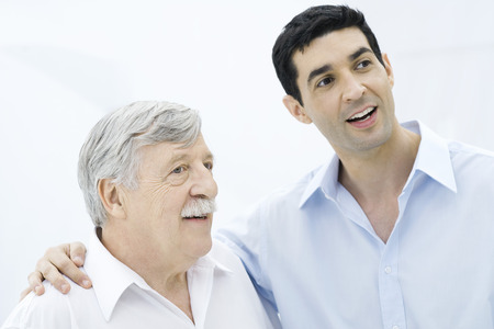distractions: Father and adult son looking away, smiling, sons arm around fathers shoulder