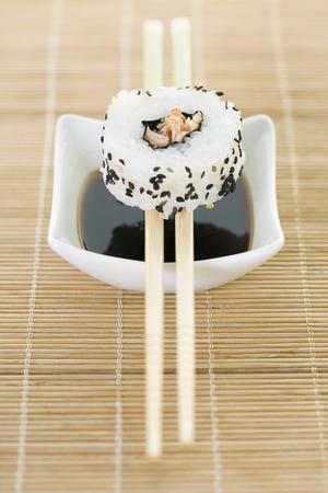 Maki sushi balanced on chopsticks over dish of soy sauce