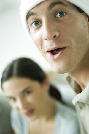 Man with open mouth looking at camera, woman smiling at camera in background