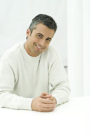 Man sitting with hands together, smiling at camera, portrait