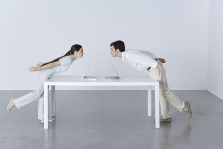plan éloigné: Man and woman at opposite ends of table, leaning towards each other, laptop computers between them