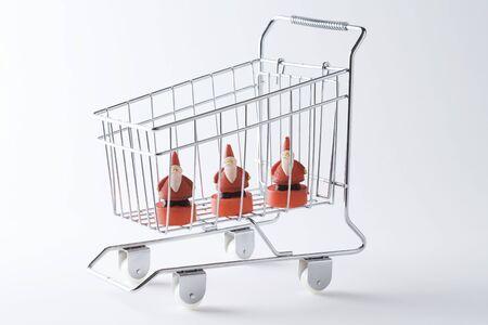 identical: Shopping cart containing three Santa Claus figurines