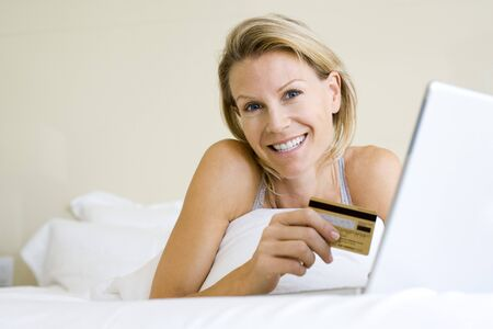tarjeta visa: Woman lying in bed with laptop computer, holding credit card, smiling at camera