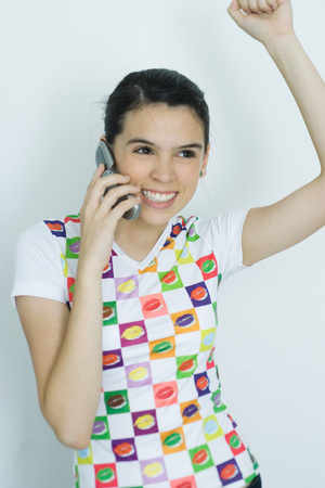 Teenage girl using cell phone and cheering, portrait