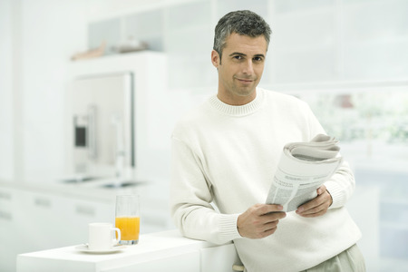 against the current: Man leaning against kitchen counter, holding newspaper, smiling at camera LANG_EVOIMAGES