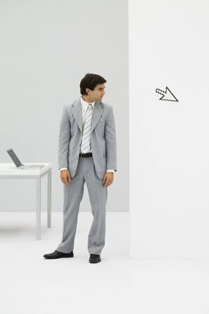 puzzlement: Businessman standing in office, looking at computer cursor pointing away