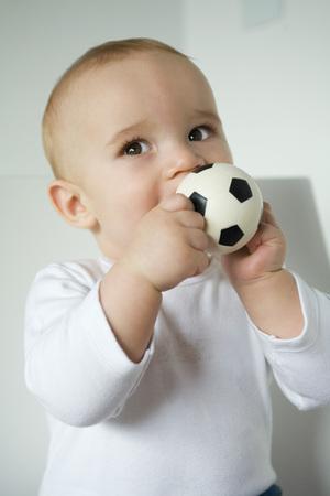 curiousness: Baby biting ball, waist up