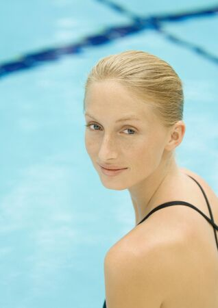beauties: Woman by pool, looking over shoulder, smiling at camera LANG_EVOIMAGES