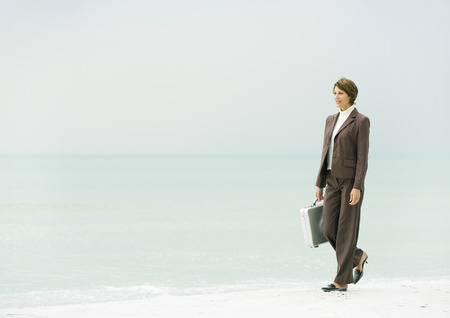 over the edge: Businesswoman walking on beach LANG_EVOIMAGES
