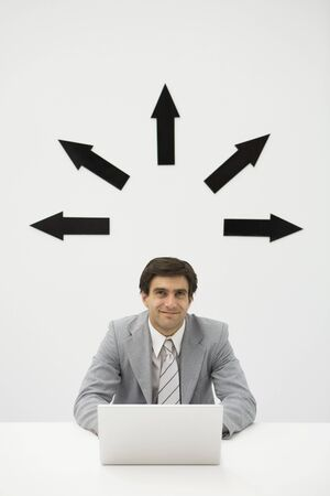distractions: Businessman sitting with laptop, smiling, arrows pointing several directions above his head