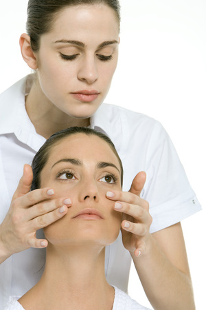 Woman receiving facial massage, looking up and away