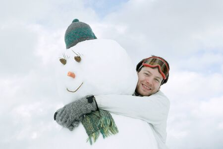 scarves: Young man hugging snowman, low angle view LANG_EVOIMAGES