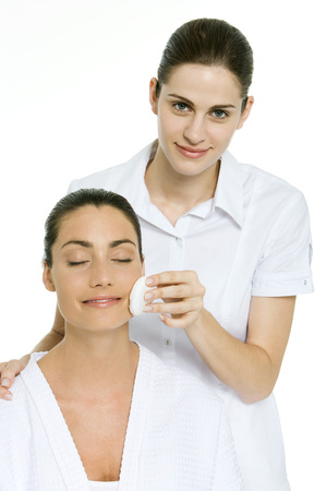 Beautician removing make-up from a woman who has her eyes closed LANG_EVOIMAGES